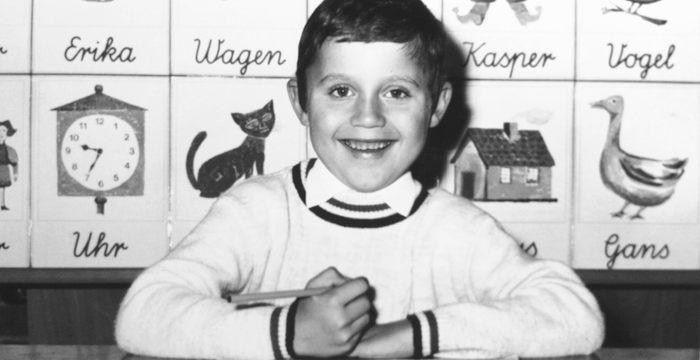 sw-Foto mit einem lachenden Schulkind am Tisch, im Hintergrund eine Alphabet-Tafel