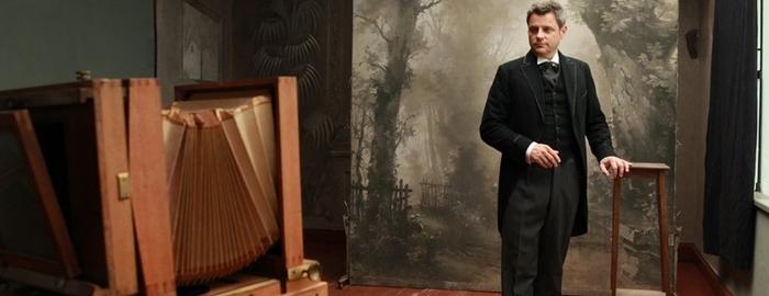 Martin von Mauschwitz in historischem Kostüm steht in einem alten Fotoatelier und lässt sich fotografieren, © TAG/TRAUM