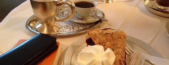 Tisch mit Kuchen, Kaffeetasse und Notizbuch