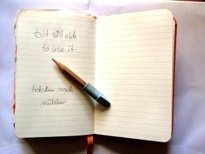 """aufgeklapptes Notizbuck mit einem Bleistift und der Notiz """"trotzdem noch nutzbar"""""""