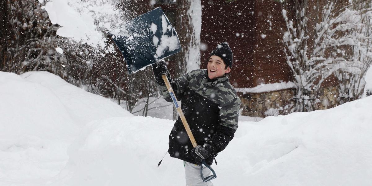 Ein Junge mit Schneeschaufel in verschneiter Landschaft